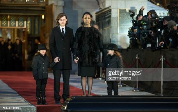 Céline Dion and her sons René-Charle Eddy and Nelson pause as the casket of her late husband René Angélil is carried to a waiting hearse following...