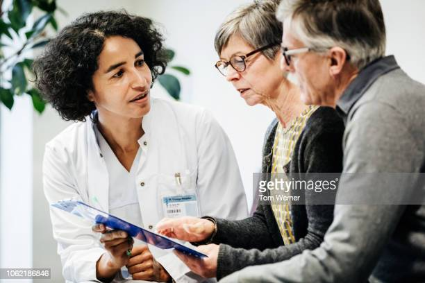 clinical doctor giving test results to patients - outpatient care stock pictures, royalty-free photos & images