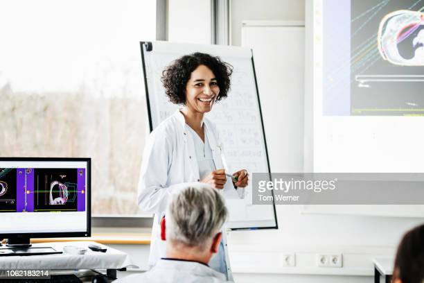 clinical doctor smiling during teaching session - laboratory coat stock pictures, royalty-free photos & images