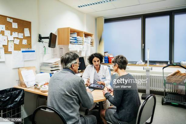 clinical doctor talking to patients - general practitioner stock pictures, royalty-free photos & images