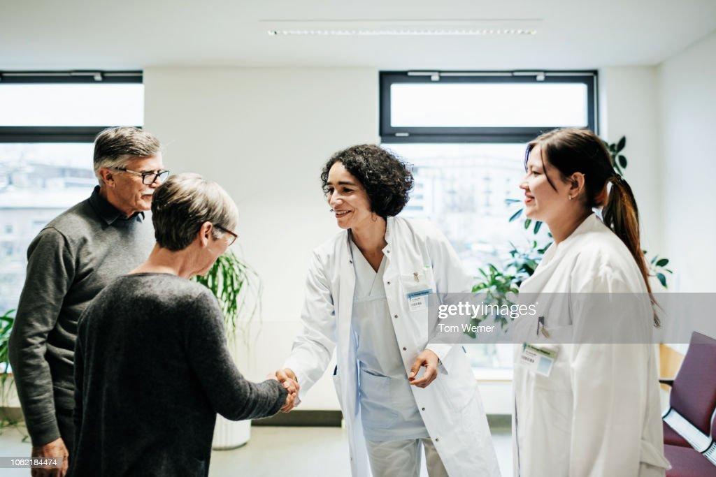 Clinical Doctors Greeting Elderly Couple : Foto de stock