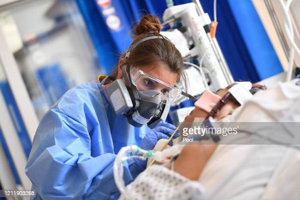 Clinical staff wear Personal Protective Equipment as they care for a patient at the Intensive Care unit at Royal Papworth Hospital on May 5 2020 in...
