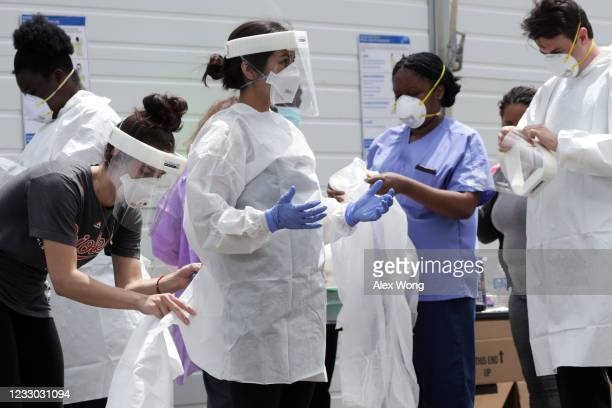 Clinicians put on personal protective equipment at a drive-thru coronavirus testing location at Six Flags America May 29, 2020 in Bowie, Maryland....