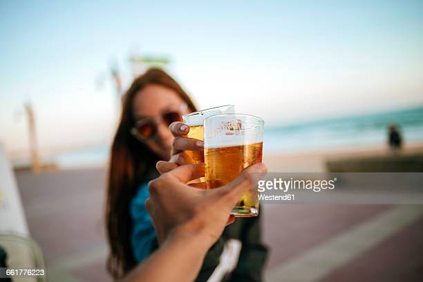 clinking beer glasses by the sea - brindisi bicchieri foto e immagini stock
