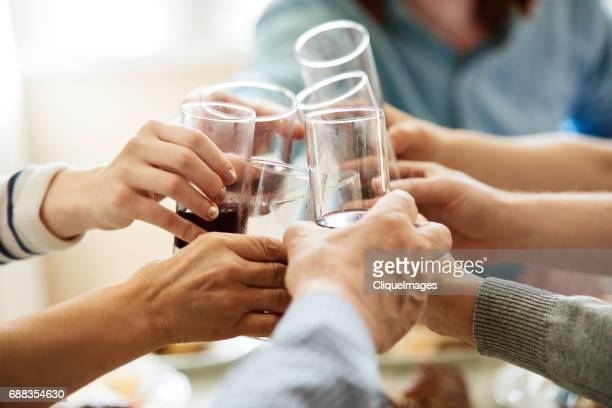 clinking glasses on family celebration - cliqueimages stockfoto's en -beelden