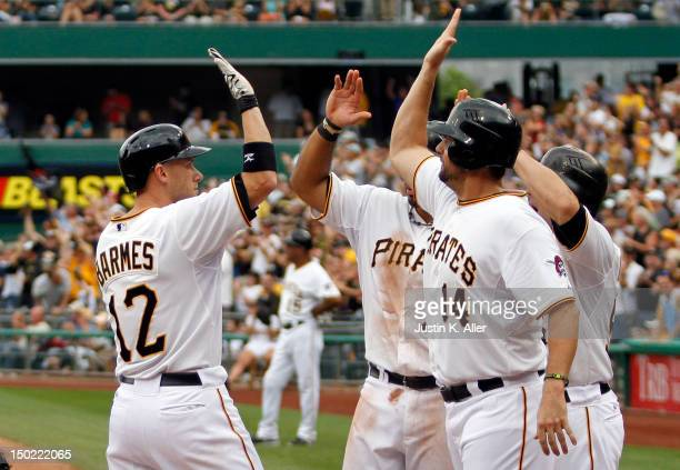 Clint Barmes of the Pittsburgh Pirates celebrates after hitting a grand slam home run with Gaby Sanchez Pedro Alvarez and Michael McKenry in the...