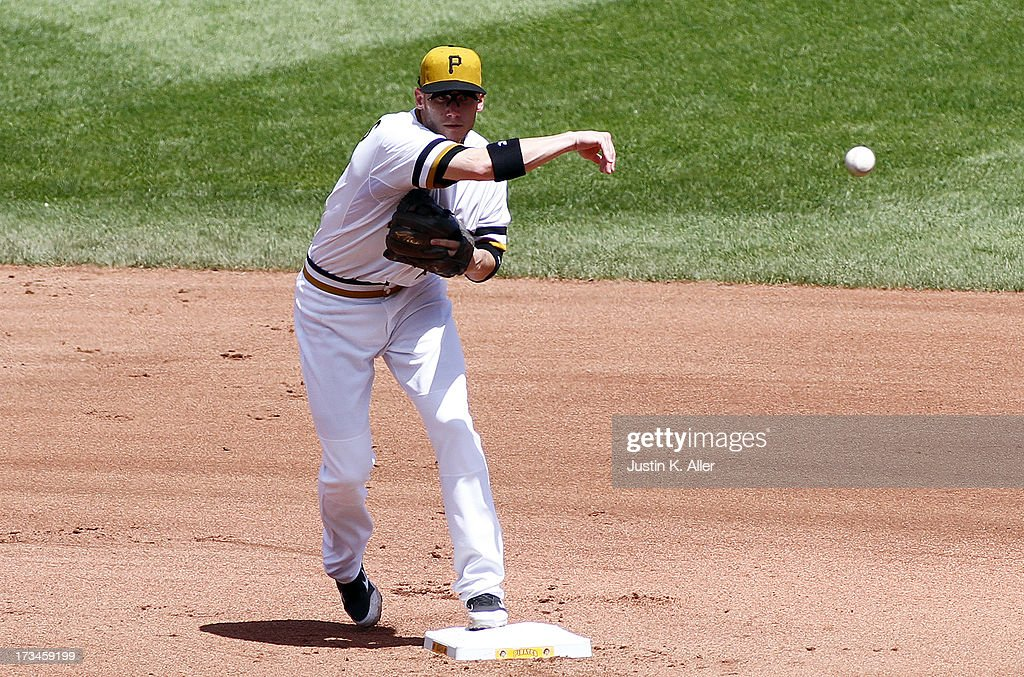 Clint Barmes #12 of the Pittsburgh Pirates makes a throw to first against the New York Mets during the game on July 14, 2013 at PNC Park in Pittsburgh, Pennsylvania. The Mets won 4-3.