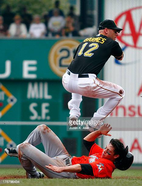 Clint Barmes of the Pittsburgh Pirates turns a double play in the third inning against Christian Yelich of the Miami Marlins during the game on...