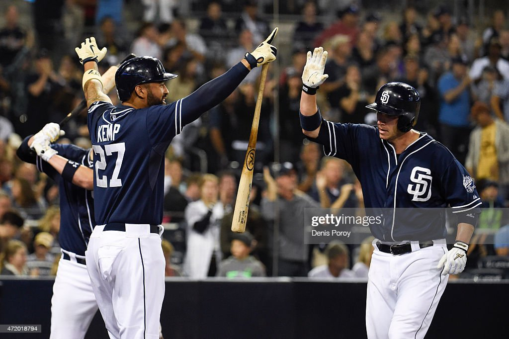 Clint Barmes #12 of the San Diego Padres is congratulated by Matt Kemp #27 after scoring during the sixth inning of a baseball game against the Colorado Rockies at Petco Park May 2, 2015 in San Diego, California.