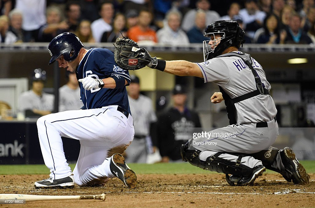 Clint Barmes #12 of the San Diego Padres scores ahead of the tag of Nick Hundley #4 of the Colorado Rockies during the sixth inning of a baseball at Petco Park May 2, 2015 in San Diego, California.