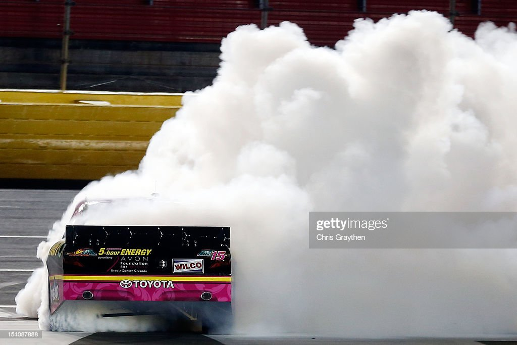 Clint Bowyer, driver of the #15 5-Hour Energy Benefiting Avon Foundation for Women Toyota, celebrates with a burnout after winning the NASCAR Sprint Cup Series Bank of America 500 at Charlotte Motor Speedway in Concord, North Carolina.
