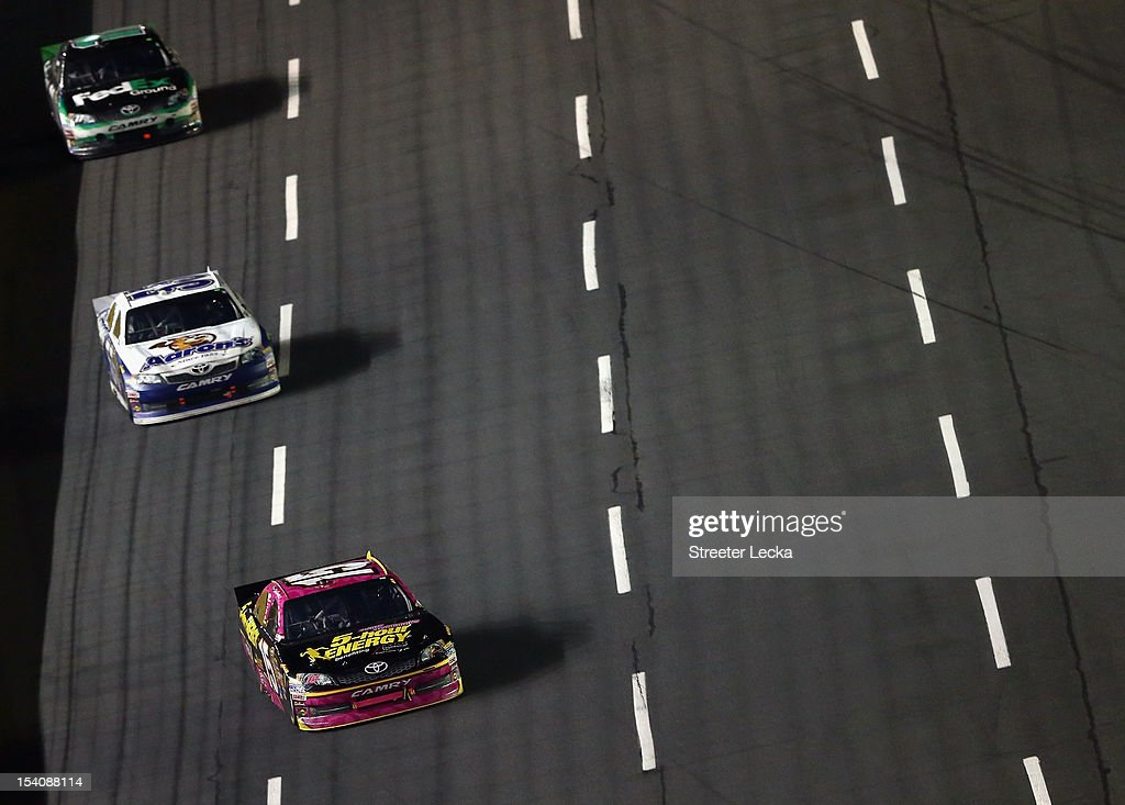 Clint Bowyer, driver of the #15 5-Hour Energy Benefiting Avon Foundation for Women Toyota, leads Mark Martin, driver of the #55 Aaron's Dream Machine Toyota, and Denny Hamlin, driver of the #11 FedEx Ground Toyota, during the NASCAR Sprint Cup Series Bank of America 500 at Charlotte Motor Speedway in Concord, North Carolina.