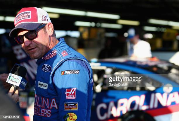 Clint Bowyer driver of the Carolina Ford Dealers Ford speaks with the media in the garage area after his engine expired during the Monster Energy...