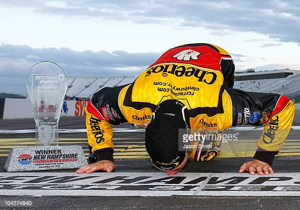 Clint Bowyer driver of the Cheerios / Hamburger Helper Chevrolet kisses the start/finish line after he won the NASCAR Sprint Cup Series Sylvania 300...