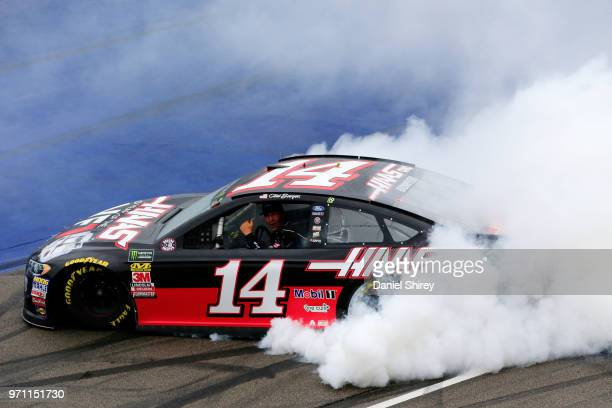 Clint Bowyer driver of the Haas 30 Years of the VF1 Ford celebrates with a burnout after winning the Monster Energy NASCAR Cup Series FireKeepers...