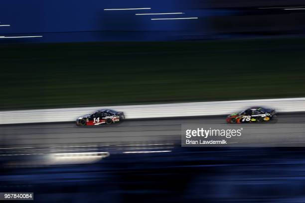 Clint Bowyer driver of the Haas 30 Years of the VF1 Ford leads Martin Truex Jr driver of the 5hour ENERGY/Bass Pro Shops Toyota during the Monster...