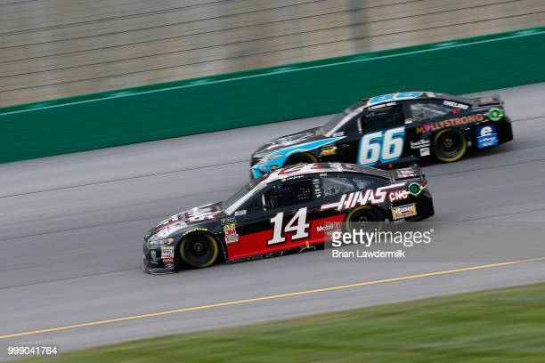 Clint Bowyer driver of the Haas 30 Years of the VF1 Ford leads Timmy Hill driver of the Crypto Crow Toyota during the Monster Energy NASCAR Cup...
