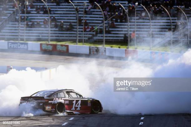Clint Bowyer driver of the Haas Automation Demo Day Ford celebrates with a burnout after winning the weather delayed Monster Energy NASCAR Cup Series...
