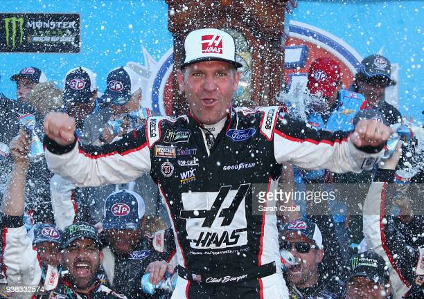 Clint Bowyer driver of the Haas Automation Demo Day Ford celebrates in Victory Lane after winning the weather delayed Monster Energy NASCAR Cup...