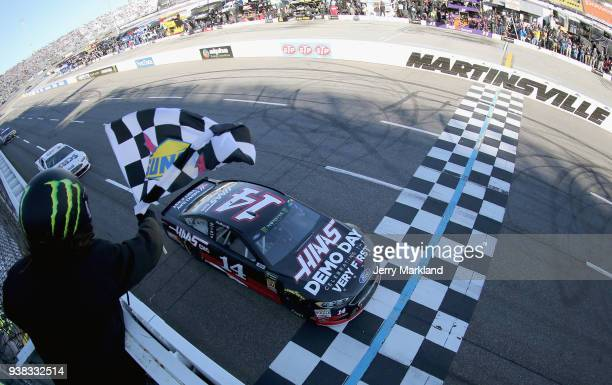 Clint Bowyer driver of the Haas Automation Demo Day Ford crosses the finish line to win the weather delayed Monster Energy NASCAR Cup Series STP 500...