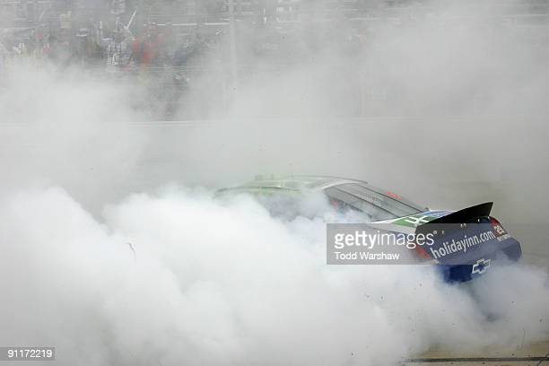 Clint Bowyer driver of the Holiday Inn Chevrolet performs a burnout after winning the NASCAR Nationwide Series Dover 200 at Dover International...