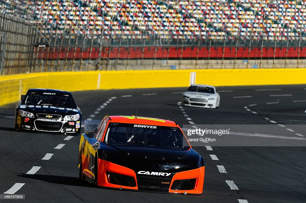 Clint Bowyer, driver of the #15 Michael Waltrip Racing Toyota, leads a pack of cars during testing at Charlotte Motor Speedway on December 11, 2013 in Charlotte, North Carolina.