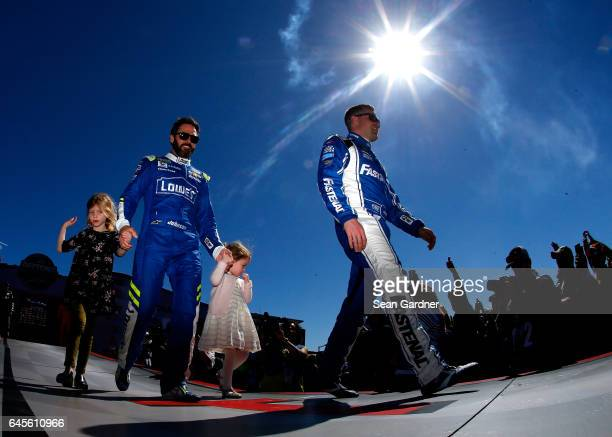 Clint Bowyer driver of the Mobil 1 Ford and Jimmie Johnson driver of the Lowe's Chevrolet with his daughters Genevieve Johnson and Lydia Norriss walk...