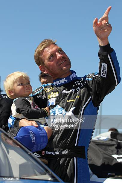 Clint Bowyer driver of the PEAK Antifreeze Coolant Toyota points to the sky with his son Cash prior to the start of the NASCAR Sprint Cup Series...