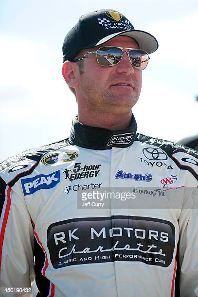 Clint Bowyer, driver of the RK Motors Charlotte Toyota, looks on from the grid during qualifying for the NASCAR Sprint Cup Series Pocono 400 at...