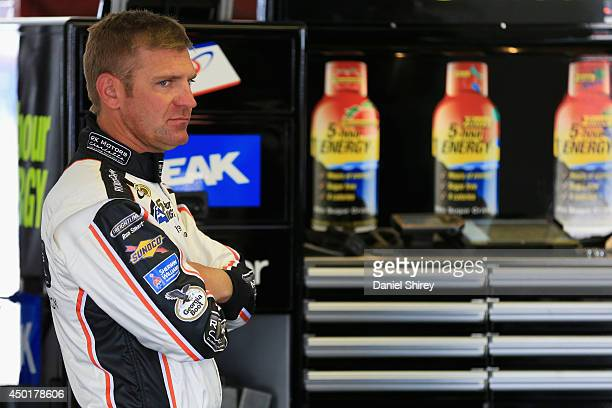 Clint Bowyer, driver of the RK Motors Charlotte Toyota, stands in the garage area during practice for the NASCAR Sprint Cup Series Pocono 400 at...