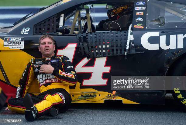 Clint Bowyer, driver of the Rush Truck Centers/Cummins Ford, exits his car and sits on the ground after the NASCAR Cup Series Bank of America ROVAL...