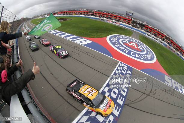 Clint Bowyer, driver of the Rush\HAAS CNC Ford, takes the green flag to start the NASCAR Cup Series Auto Club 400 at Auto Club Speedway on March 01,...
