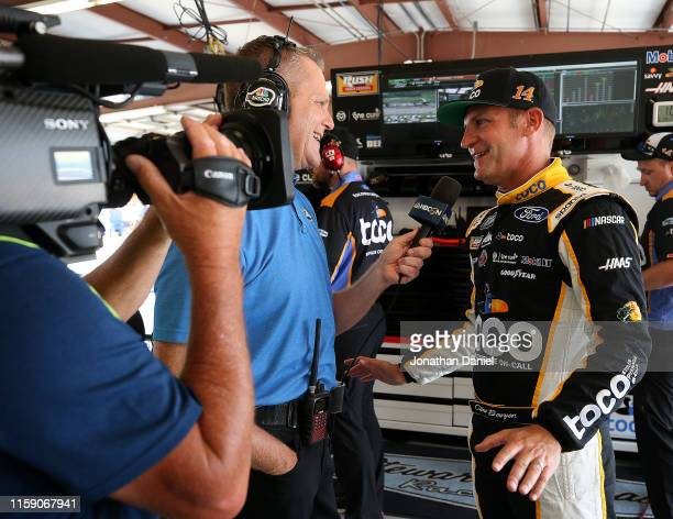 Clint Bowyer driver of the Toco Warranty Ford is interviewed in the garage during practice for the Monster Energy NASCAR Cup Series Camping World 400...