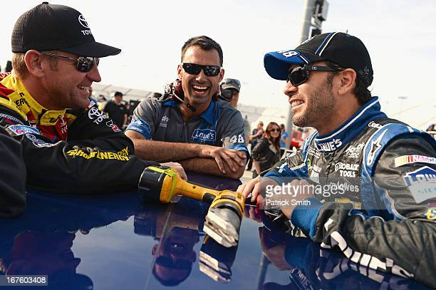 Clint Bowyer driver of the Toyota Care Toyota and Jimmie Johnson driver of the Lowe's Dover White Chevrolet talk on the grid during qualifying for...