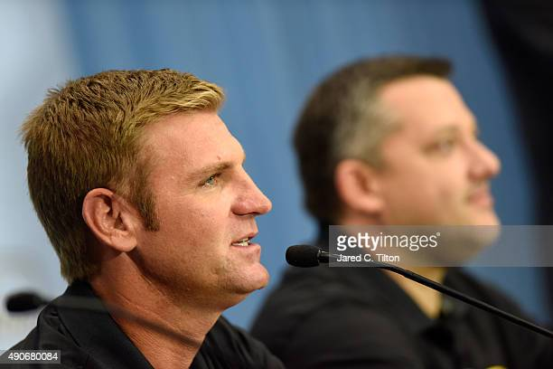 Clint Bowyer speaks with the media as Tony Stewart driver of the StewartHaas Racing Chevrolet and coowner of StewartHaas Racing looks on during a...