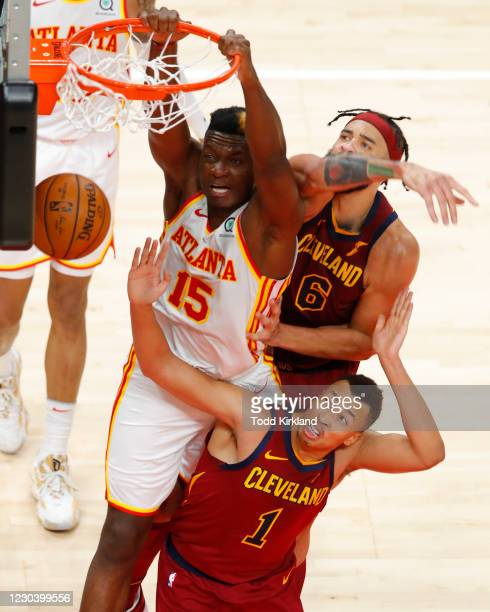 Clint Capela of the Atlanta Hawks dunks as JaVale McGee and Dante Exum of the Cleveland Cavaliers defend during the first half at State Farm Arena on...