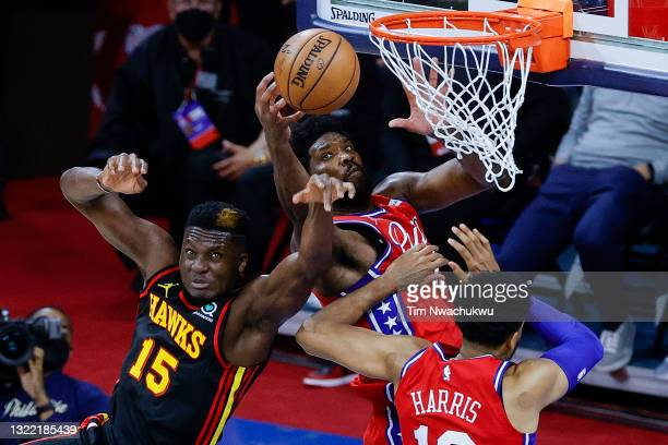 Clint Capela of the Atlanta Hawks tangles with Joel Embiid of the Philadelphia 76ers during the fourth quarter during Game One of the Eastern...