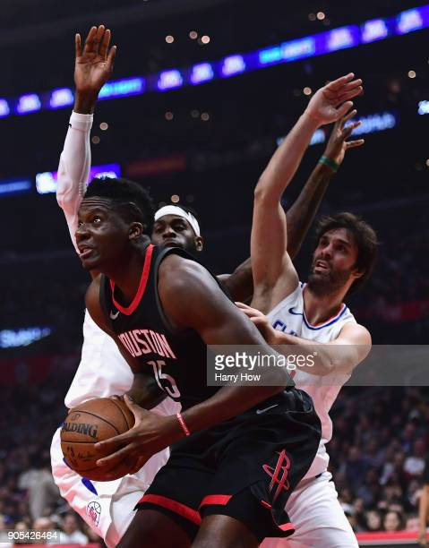 Clint Capela of the Houston Rockets attempts a shot as he is guarded by Willie Reed and Milos Teodosic of the LA Clippers during the first half at...