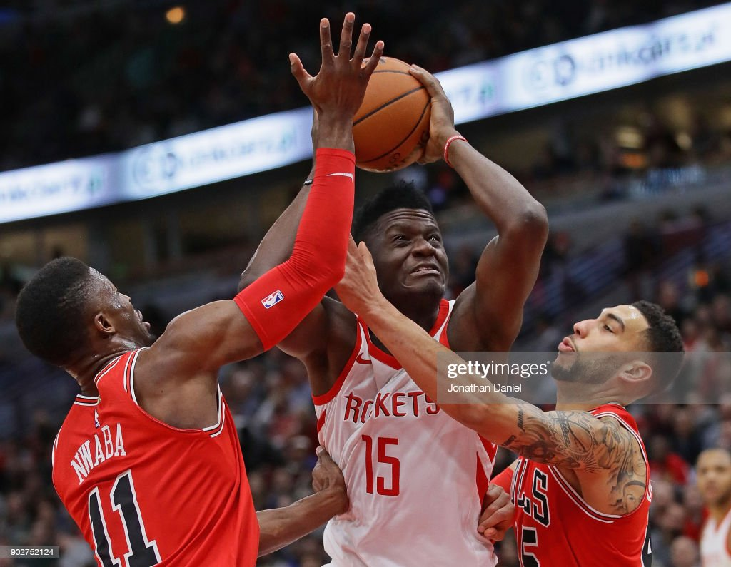 Clint Capela #15 of the Houston Rockets drives between David Nwaba #11 and Denzel Valentine #45 of the Chicago Bulls at the United Center on January 8, 2018 in Chicago, Illinois.