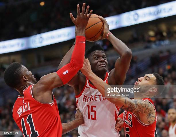 Clint Capela of the Houston Rockets drives between David Nwaba and Denzel Valentine of the Chicago Bulls at the United Center on January 8 2018 in...