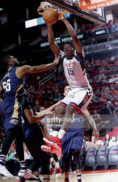 Clint Capela of the Houston Rockets dunks over E'Twaun Moore of the New Orleans Pelicans as Alexis Ajinca looks on at Toyota Center on December 16...