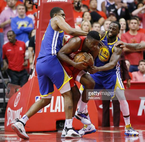Clint Capela of the Houston Rockets is double teamed by Draymond Green of the Golden State Warriors and Kevon Looney during Game Six of the Western...
