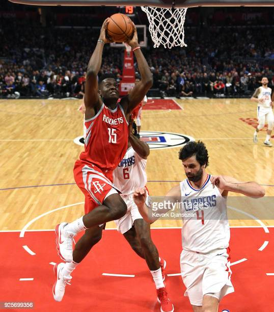 Clint Capela of the Houston Rockets leaps for a slam dunk against Milos Teodosic and DeAndre Jordan of the Los Angeles Clippers during the second...