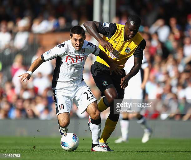 Clint Dempsey of Fulham holds off a challenge from Christopher Samba of Blackburn Rovers during the Barclays Premier League match between Fulham and...