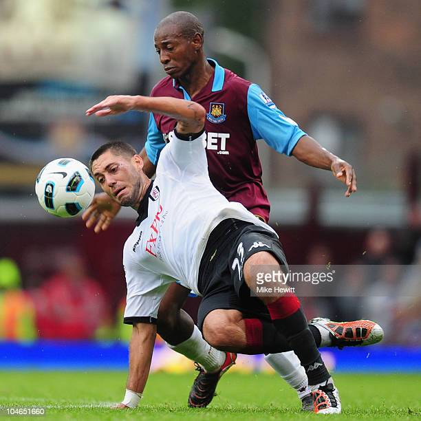 Clint Dempsey of Fulham is challenged by Luis Boa Morte of West Ham during the Barclays Premier League match between West Ham United and Fulham at...