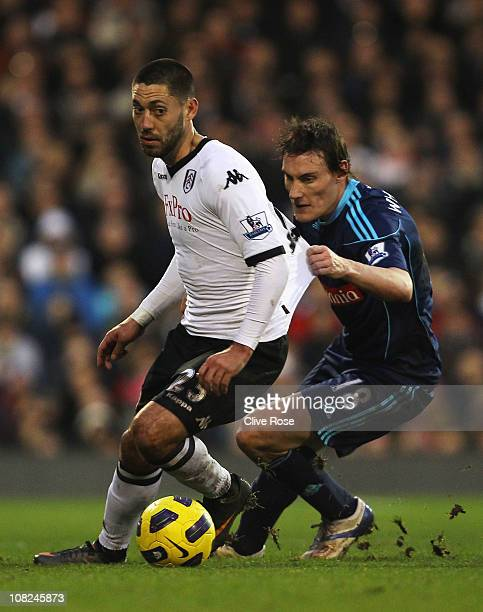 Clint Dempsey of Fulham is held back by Dean Whitehead of Stoke City during the Barclays Premier League match between Fulham and Stoke City at Craven...