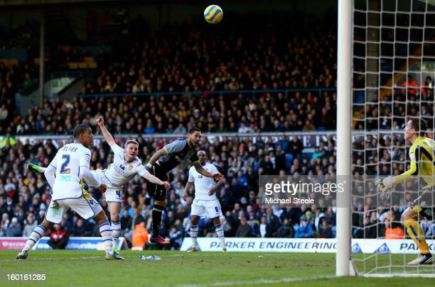 Clint Dempsey of Spurs rises above Tom Lees of Leeds to head his team's opening goal during the FA Cup with Budweiser Fourth Round match between...