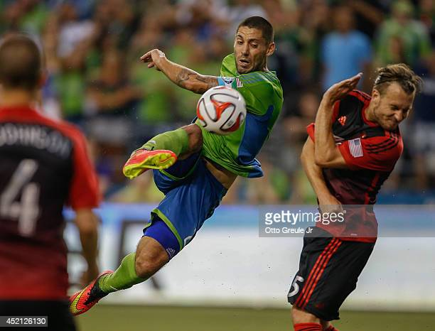 Clint Dempsey of the Seattle Sounders takes a shot against Michael Harrington against the Portland Timbers at CenturyLink Field on July 13 2014 in...