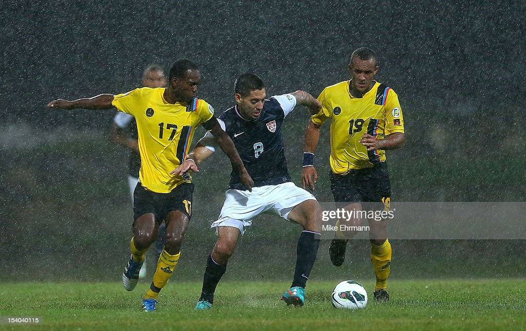 Clint Dempsey #8 of the United States fights for a ball against Luke Anthony George #19 and George Dublin #17 of Antigua and Barbuda during a World Cup Qualifying game at Sir Vivian Richards Stadium on October 12, 2012 in Antigua, Antigua and Barbuda.