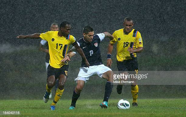 Clint Dempsey of the United States fights for a ball against Luke Anthony George and George Dublin of Antigua and Barbuda during a World Cup...